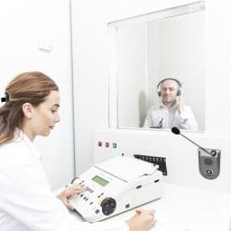 Patient receiving a hearing test in a booth