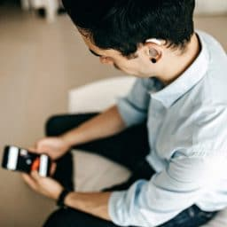 Relaxed Businessman Using Phone in Hotel Room wearing a hearing aid