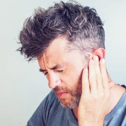Man with earache is holding his aching ear body pain concept