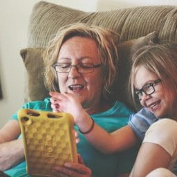 Older adult female and young girl play with a tablet while sitting in a recliner