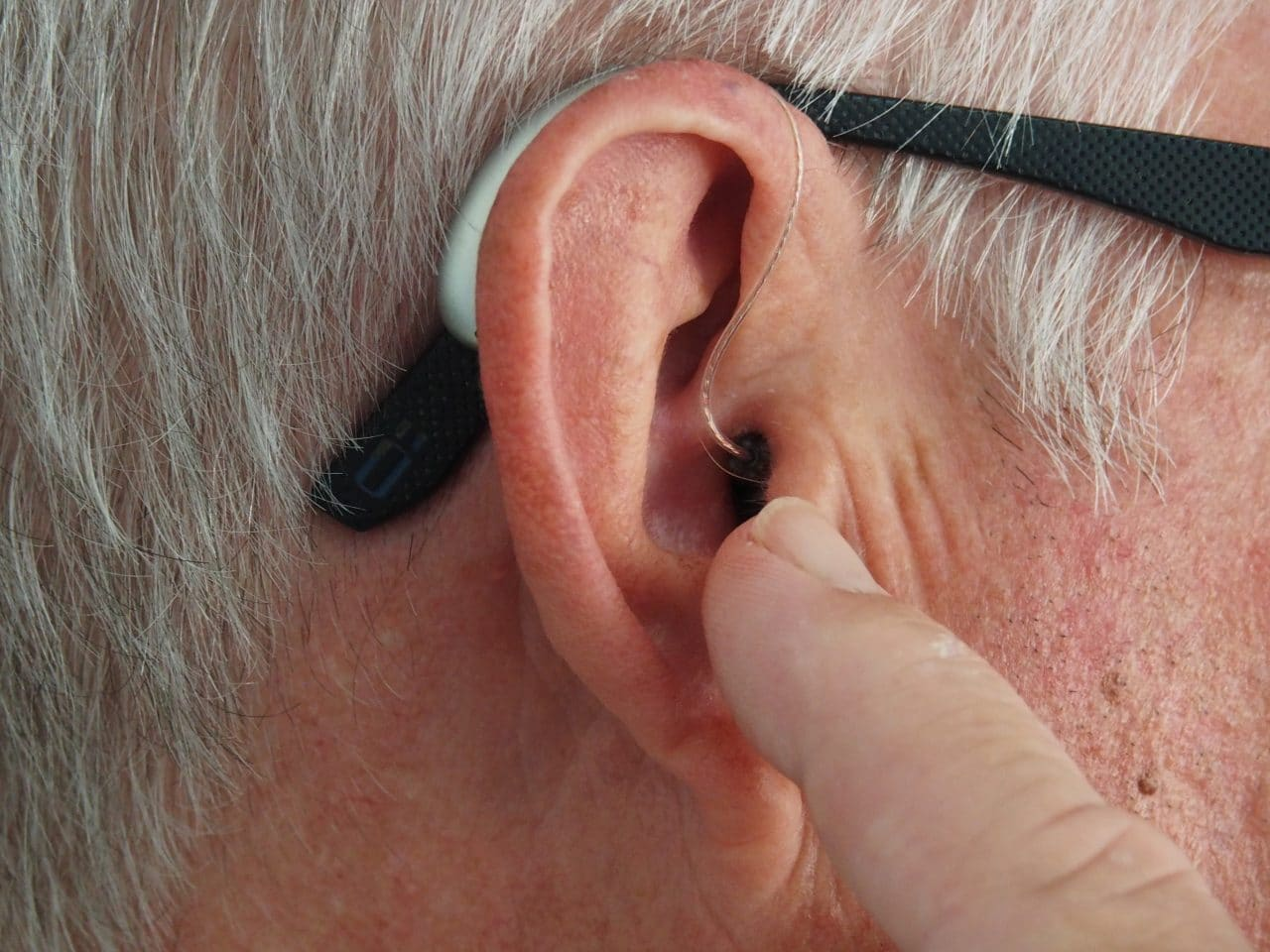 Man points at hearing aid on ear