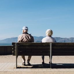 A couple sitting at a bench.