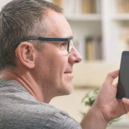 Man with hearing aid uses a phone.